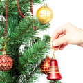 Female hand with red bell and Christmas tree. - PhotoDune Item for Sale