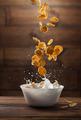 Falling corn flakes with milk splash on wood - PhotoDune Item for Sale