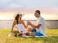 smiling couple with small red gift box on picnic - PhotoDune Item for Sale