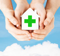 hands holding paper house with green cross - PhotoDune Item for Sale