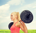 smiling sporty woman exercising with barbell - PhotoDune Item for Sale