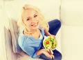 smiling young woman with green salad at home - PhotoDune Item for Sale