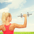 sporty woman with heavy steel dumbbell from back - PhotoDune Item for Sale