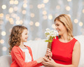 happy little daughter giving flowers to her mother - PhotoDune Item for Sale