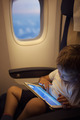 Boy spending time with tablet PC during flight - PhotoDune Item for Sale