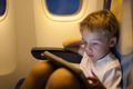 Boy sitting in the plane and using tablet PC - PhotoDune Item for Sale