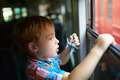 Little boy with toy looking out of train window - PhotoDune Item for Sale