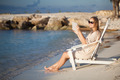 Woman with pad relaxing in chaise-lounge on the beach - PhotoDune Item for Sale