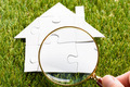 Finger Holding Magnifying Glass Over Puzzle House - PhotoDune Item for Sale