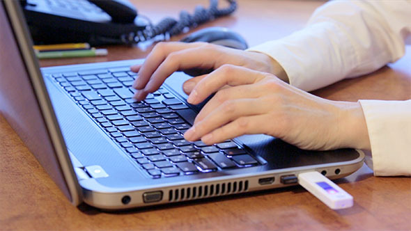 Woman Using Laptop and Inserting USB Flash Drive