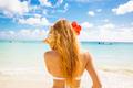 Beautiful woman with sea shell enjoying beach listening to ocean sound