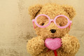 love ly bear doll wearing pink glasses and holding pink heart shape - PhotoDune Item for Sale