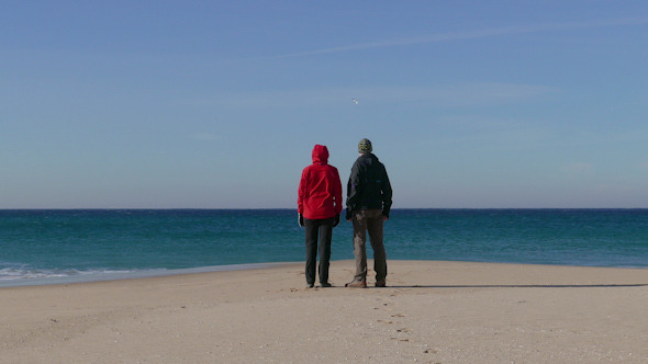 Happy Middle-aged Couple Walking on Beach