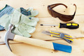 Some working tools with protective gloves and glasses lie on wooden background - PhotoDune Item for Sale