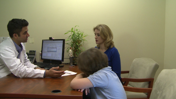 Male Doctor Consults With Mother And Son 5 Of 7