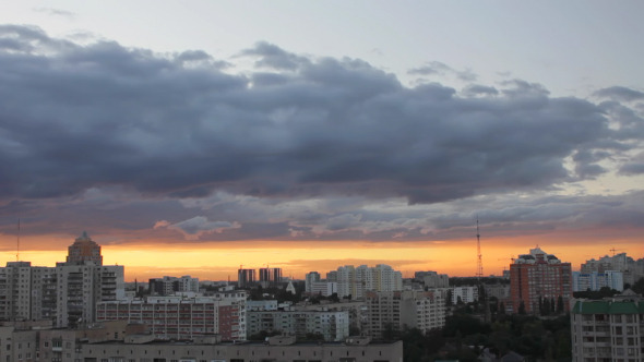 Time-lapse of passing clouds at sunset over city