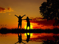 Silhouette happy excited carefree couple looking at sunset