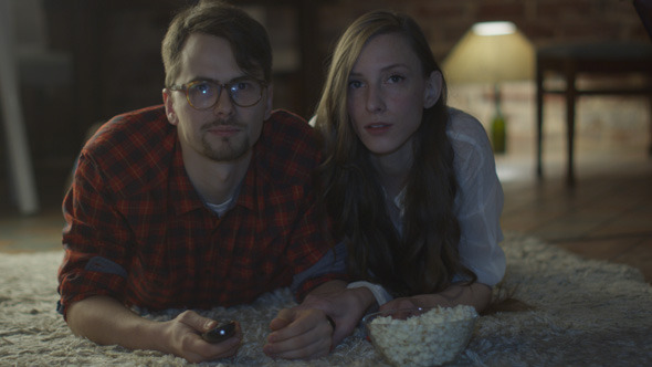 Young Couple are Watching TV and Eating Popcorn 2