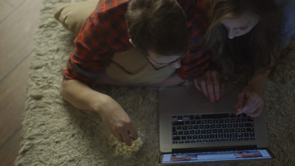Young Couple are Laying on Floor and Using Laptop