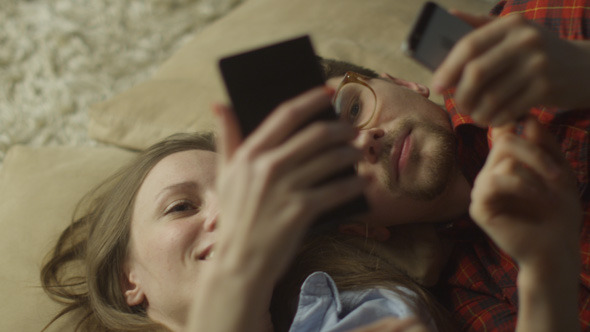 Couple are Laying on the Floor and Using Phones
