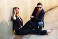Young fashion couple sitting at the wall - PhotoDune Item for Sale