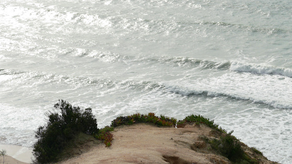 Man Climb on a Cliff Above the Ocean