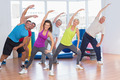 Full length of fit people doing stretching exercise in gym