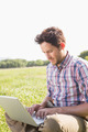 Young man using laptop in the countryside on a sunny day