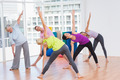 Full length of women doing stretching exercise in gym