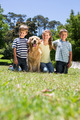 Happy siblings with their dog on a sunny day