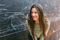 Young beautiful woman standing in front a blackboard wall. - PhotoDune Item for Sale