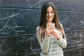 Young beautiful woman using phone in front a blackboard wall. - PhotoDune Item for Sale