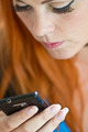 Red hair girl looking at her phone - PhotoDune Item for Sale