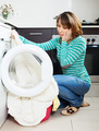 Unhappy woman cheking  clothes near washing machine - PhotoDune Item for Sale