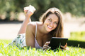 Girl lying on grass with ereader - PhotoDune Item for Sale