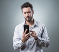 Disappointed man typing with his smartphone - PhotoDune Item for Sale