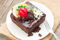 Piece of chocolate cake with icing and fresh berry on wooden bac - PhotoDune Item for Sale
