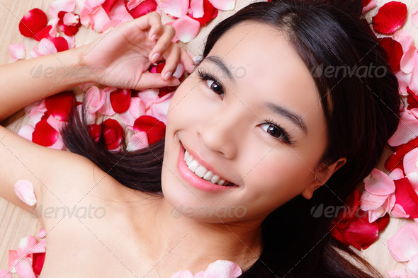 Asian beauty Girl smiling touching her face with rose background - Stock Photo - Images