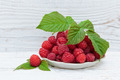 Raspberries in a bowl on a wooden white table - PhotoDune Item for Sale