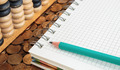 Notepad with pencil and abacus on a pile of coins - PhotoDune Item for Sale