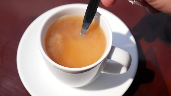 Male Hand Stir Milk In Cup Of Tea