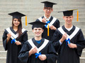 young students in graduation gowns on university campus - PhotoDune Item for Sale