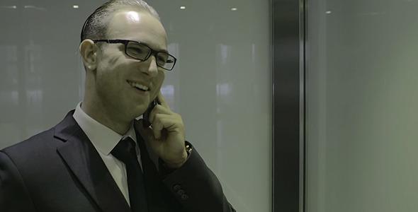 Businessman Talking On Phone In Elevator