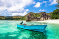 Old fishing boat on a Tropical beach at Curieuse island Seychell - PhotoDune Item for Sale
