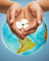 cupped hands holding euro coins over earth globe - PhotoDune Item for Sale