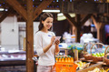 happy woman with food basket and notepad in market - PhotoDune Item for Sale