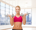 smiling woman with dumbbells flexing biceps in gym - PhotoDune Item for Sale