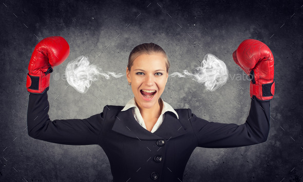 Businesswoman in boxing gloves posing with her arms up, shouting, smoke from ears