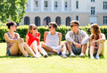 group of smiling friends outdoors sitting on grass - PhotoDune Item for Sale