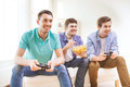 smiling friends playing video games at home - PhotoDune Item for Sale